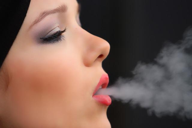 Kobieta wydmuchuje dym